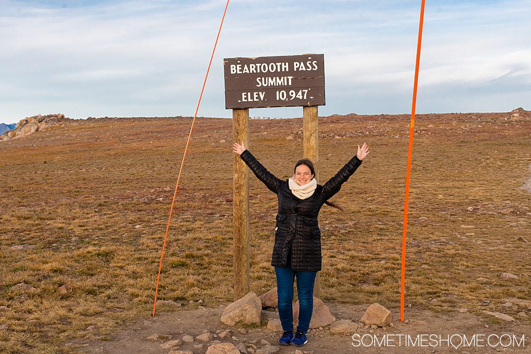 Woman with raised arms posing for a photo with the highest elevation marker of Beartooth Highway in Montana.