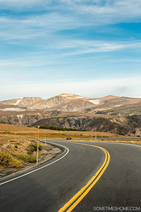 A winding road and snow-capped mountains in the background of Beartooth Pass in Montana and Wyoming.