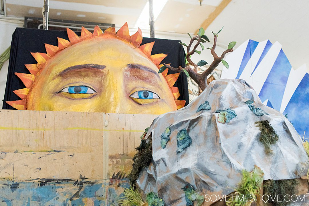 Paper mache sun peeking over to a mountain and tree