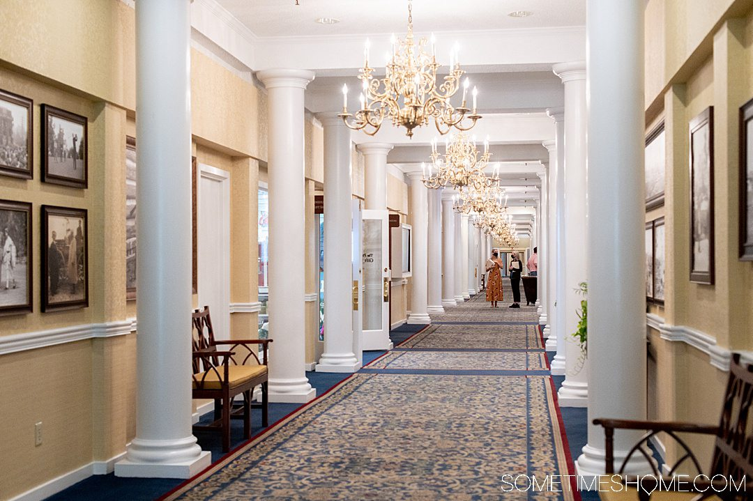 An interior hallway of the Carolina Hotel in Pinehurst, NC with white columns and historic photos on the walls.