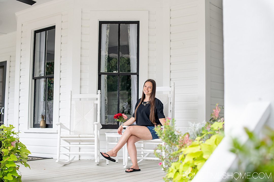 A woman sitting on the porch of a historic hotel, The Magnolia Inn, in Pinehurst, NC.