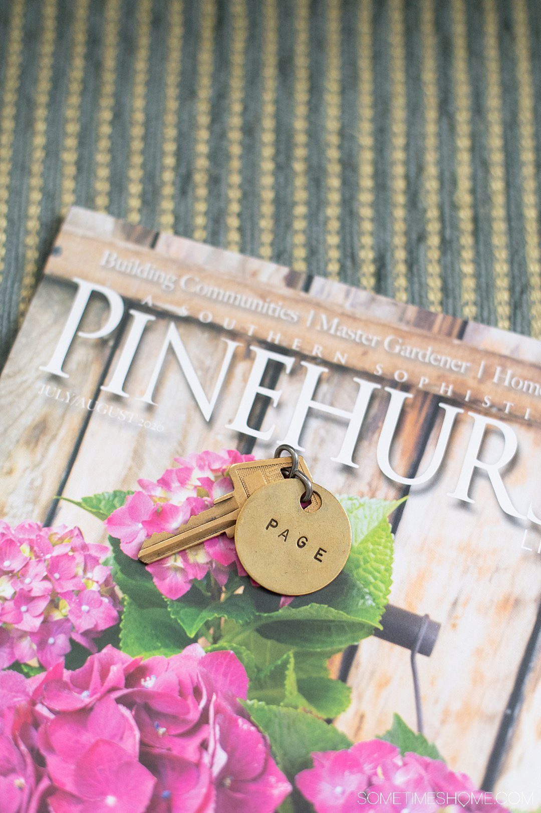 "History of Pinehurst, NC seen here in a magazine cover with pink hydrangea flowers on it and a key chain that reads, ""Page."""