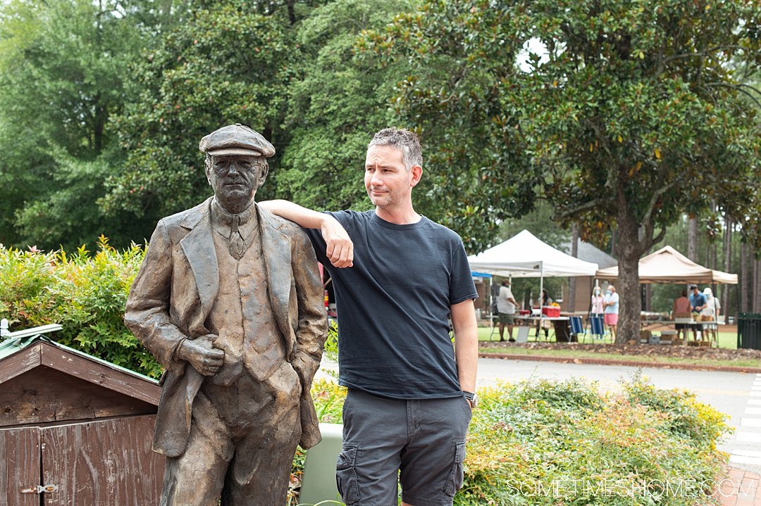 A statue of Donald Ross and a man visiting the Village of Pinehurst, NC.