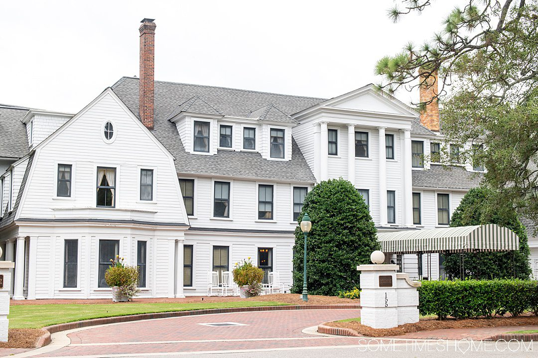 The historic hotel, The Holly Inn, in Pinehurst, NC. It is a three story white building.
