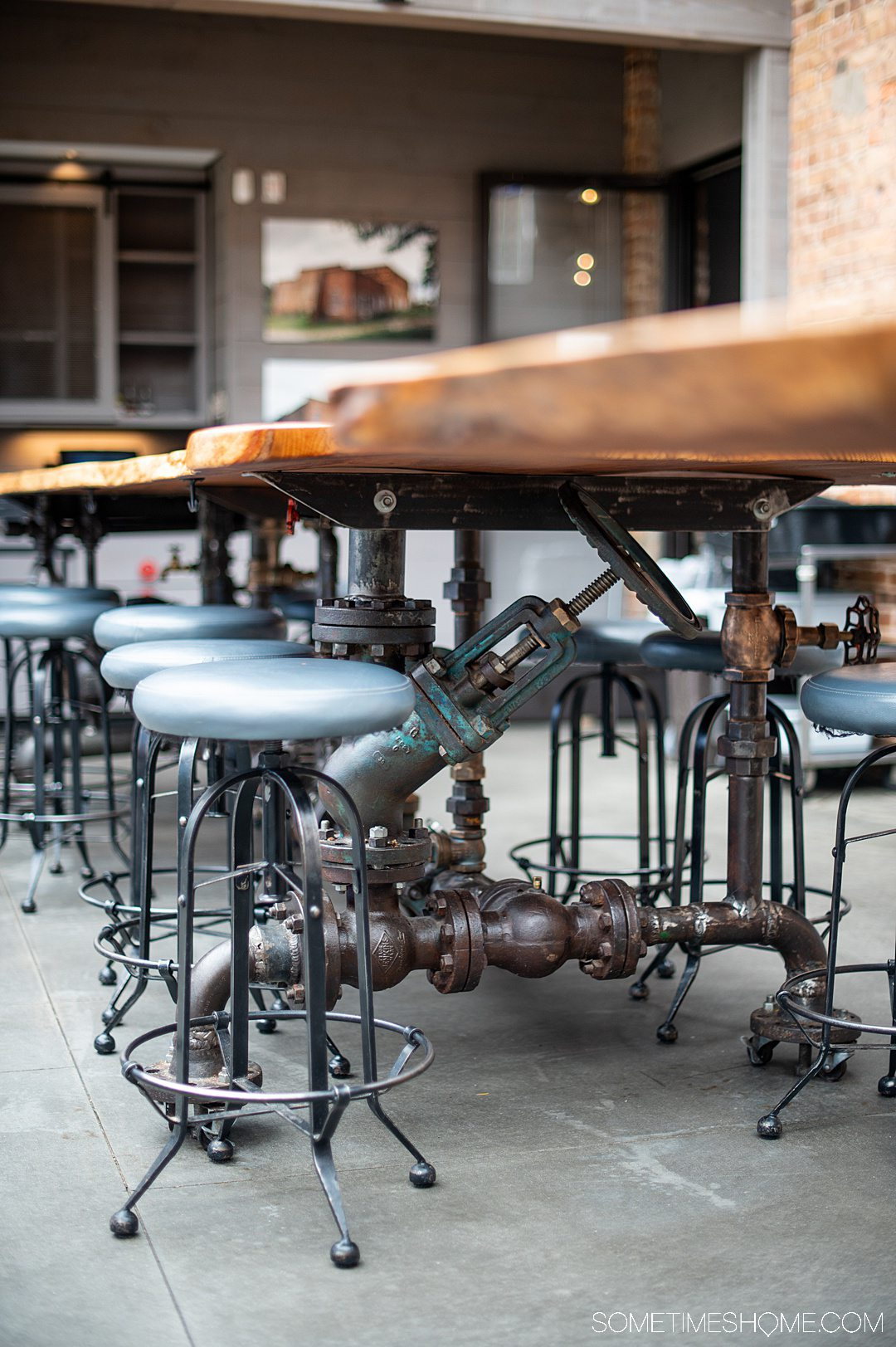 Photo of bar stools and a table at Pinehurst Brewing Co. made with pipes and valves.