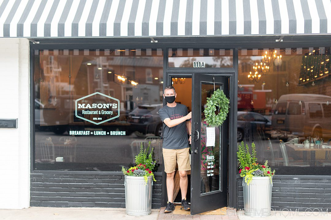 A man coming outside a restaurant with a black and white striped awning.