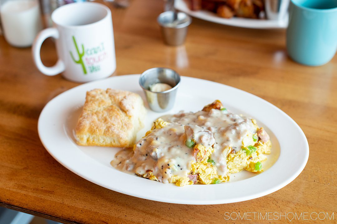 A plate of food: eggs with white gravy on it and a biscuit on the side.
