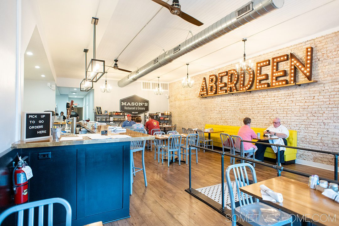 "The inside of a restaurant with white painted brick walls and ""ABERDEEN"" letters on the wall."