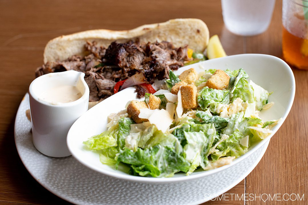 Photo of a Philly Cheesesteak and Caesar salad at The Deuce restaurant in Pinehurst, NC.