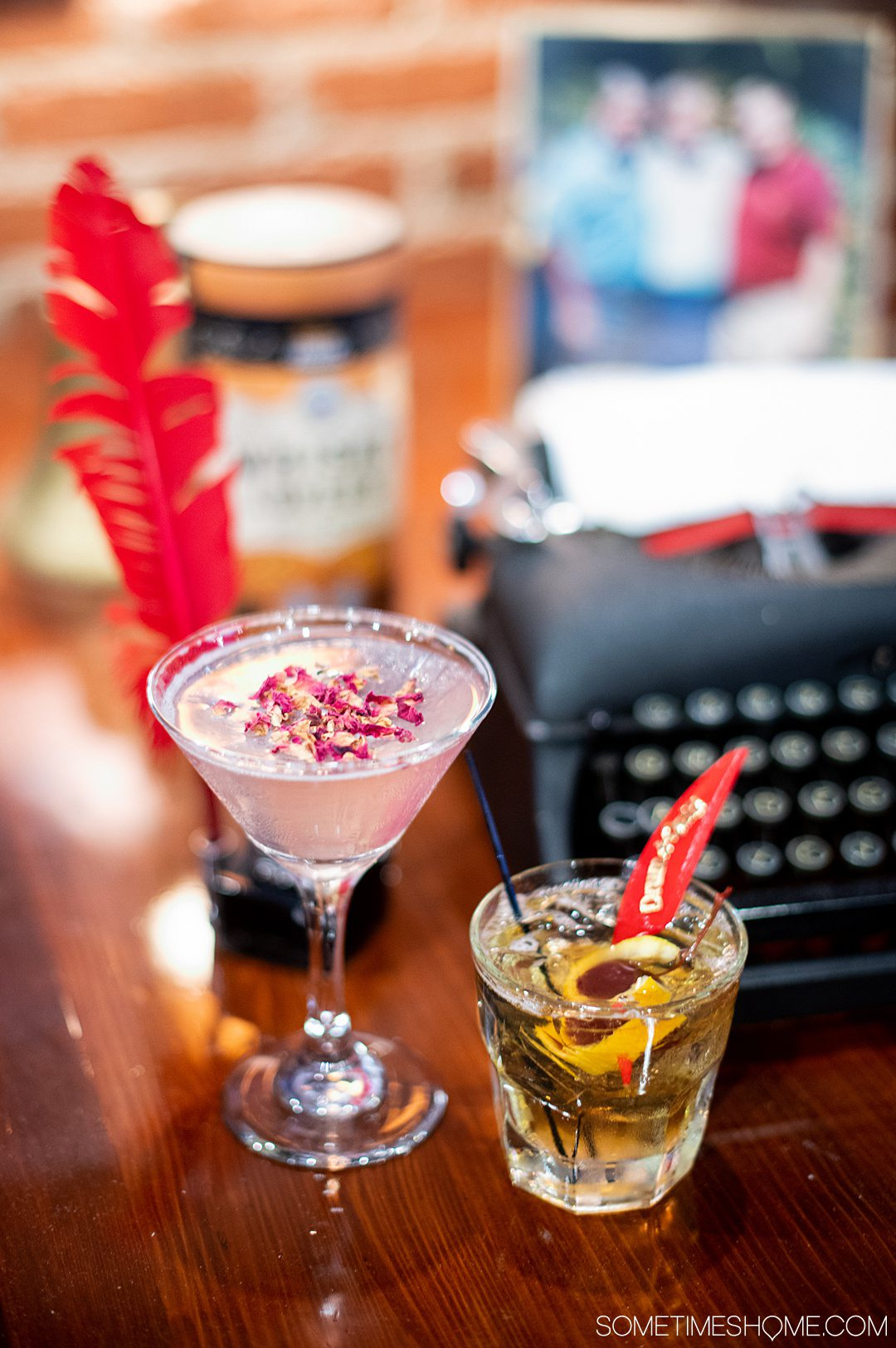 Two cocktails with a typewriter and feather quill behind it.