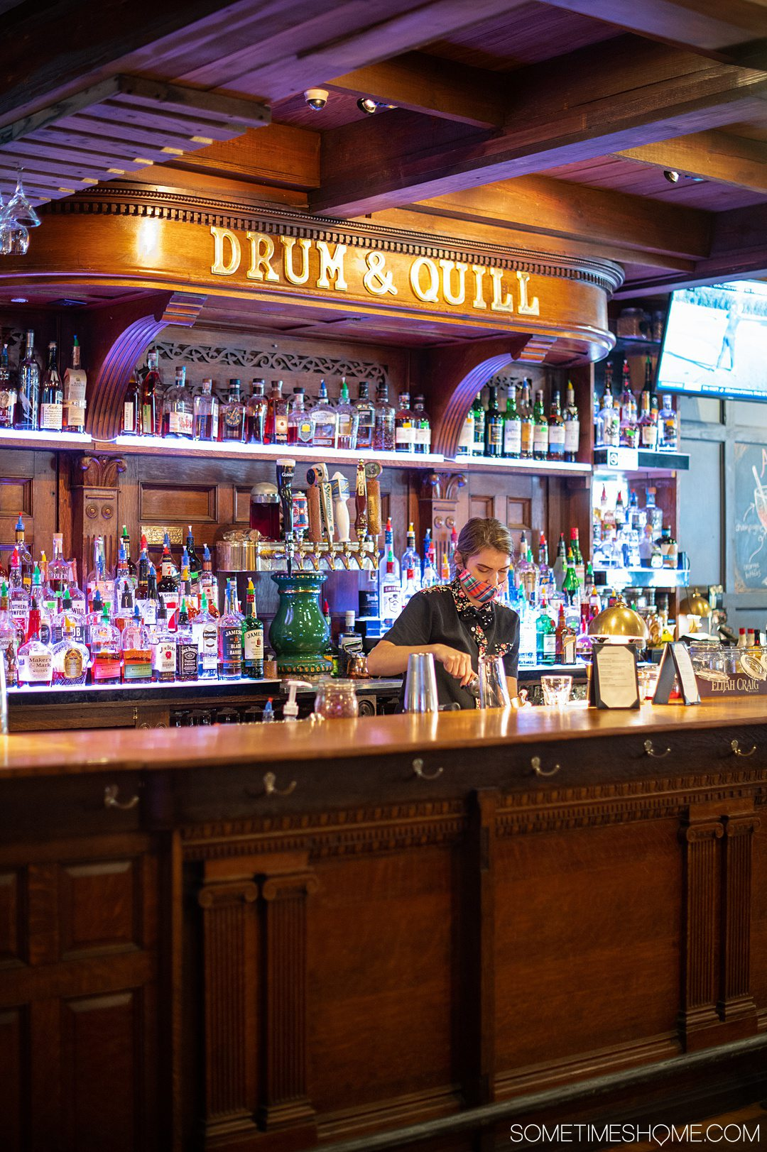 A woman bartending behind the wood bar at Drum & Quill.