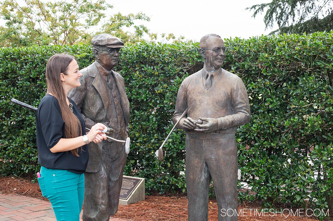 A woman with two bronze golfer statues at Pinehurst Resort in North Carolina.