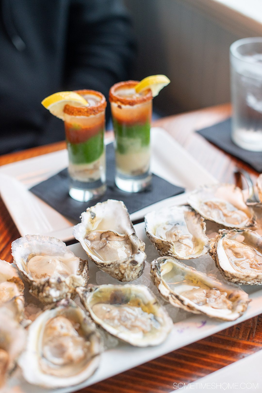 A plate of raw oysters with two oyster shooters in the background at the Blue Water Grill & Raw Bar in the Outer Banks.