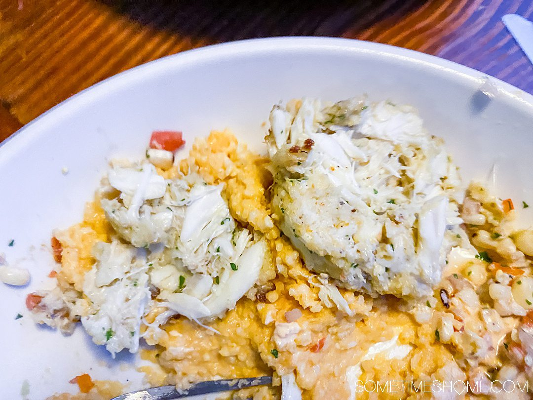 Lump crab cakes on top of cheesy grits at one of the best seafood restaurants in the Outer Banks.