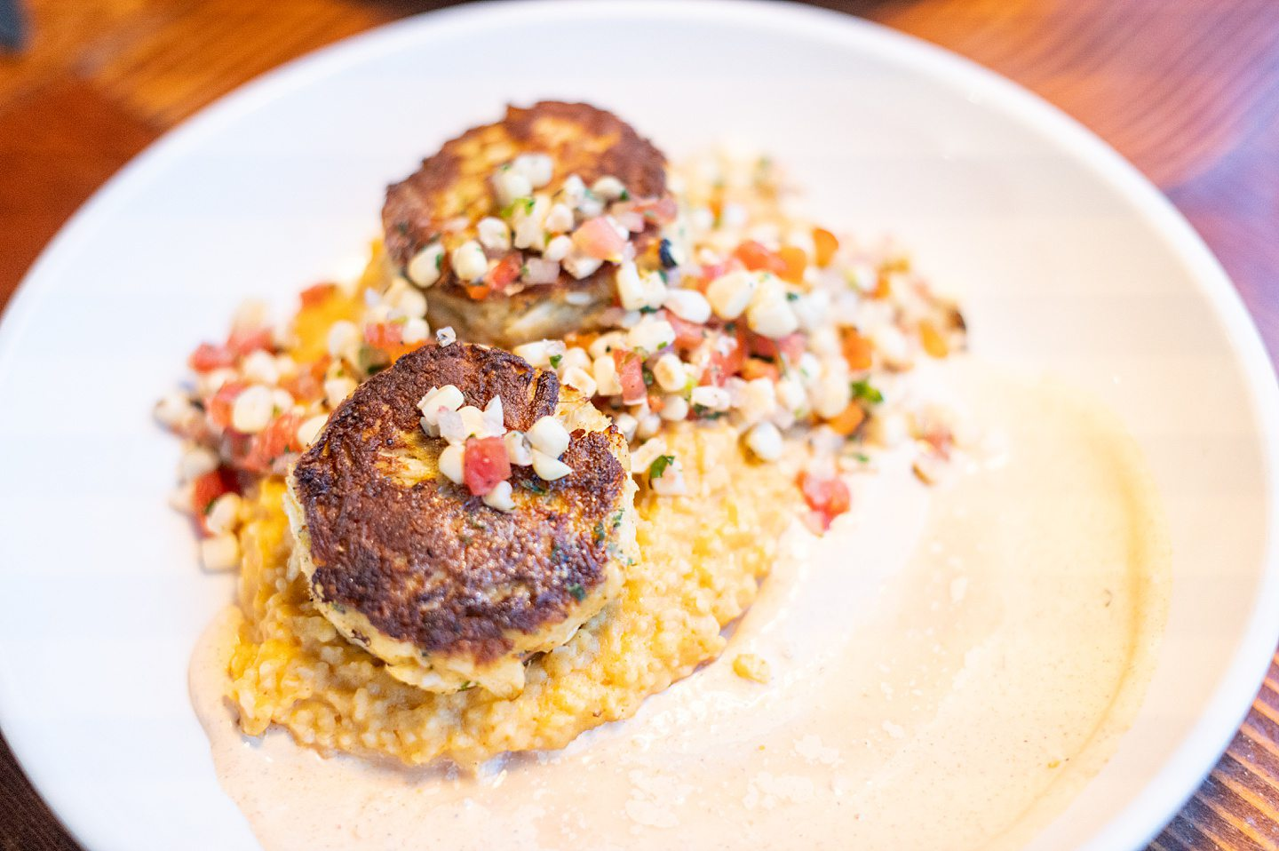 two lump crab cakes on top of cheesy grits with a corn salsa at Blue Water Grill in Manteo, NC.