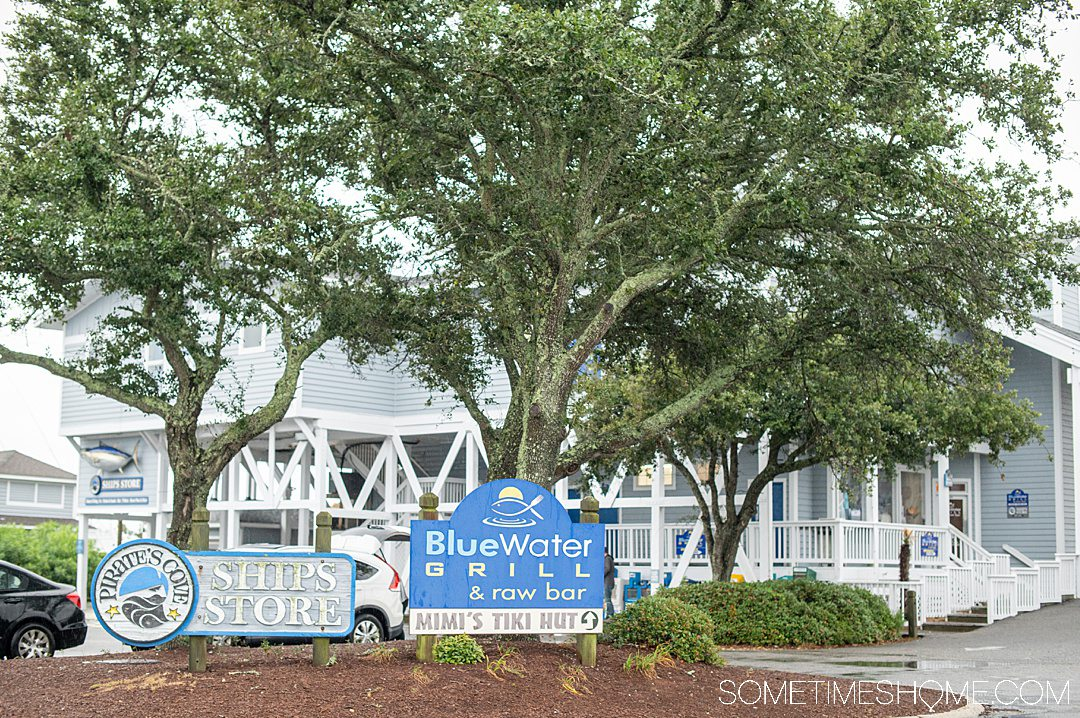 "Trees and a restaurant behind it. A sign out front reads, ""Blue Water Grill & Raw Bar"" in the Outer Banks."