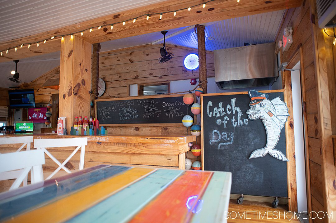 "Colorful interior of a restaurant with ""Catch of the Day"" written on the blackboard and a characterized fish next to it. Buoys are the left of the board at this best seafood restaurant in the Outer Banks."