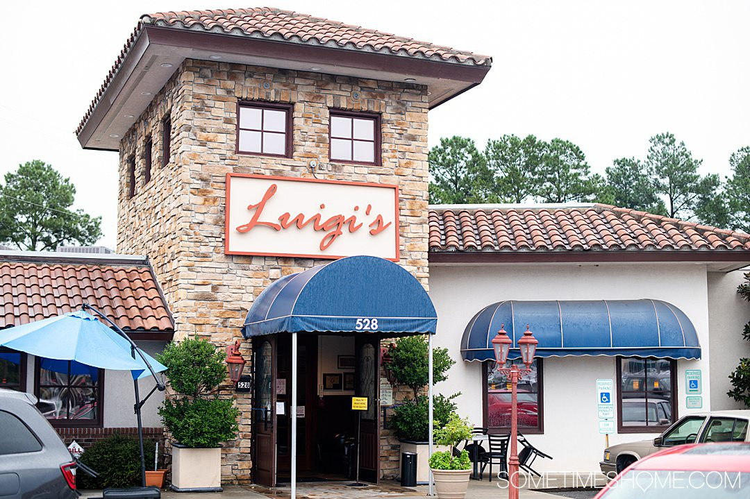 "A restaurant facade with ""Luigi's"" on a sign above a blue awning in Fayetteville, NC."