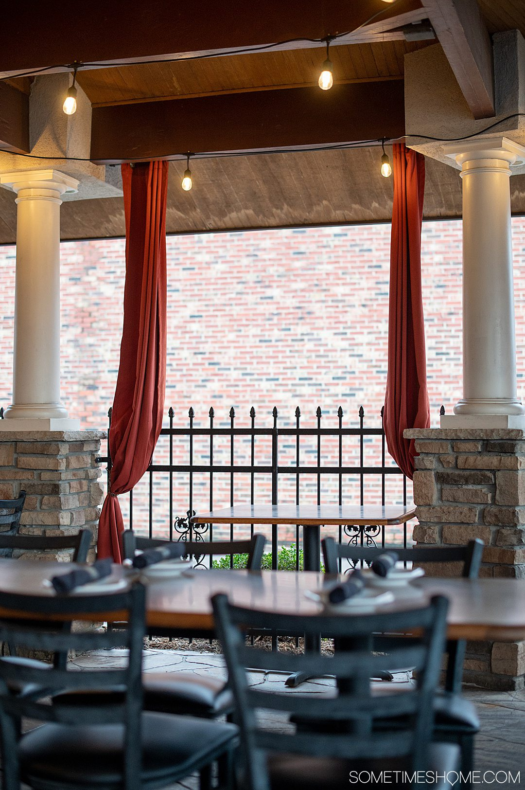 Red curtains and white columns on an outdoor patio at the restaurant Luigi's in Fayetteville, NC.