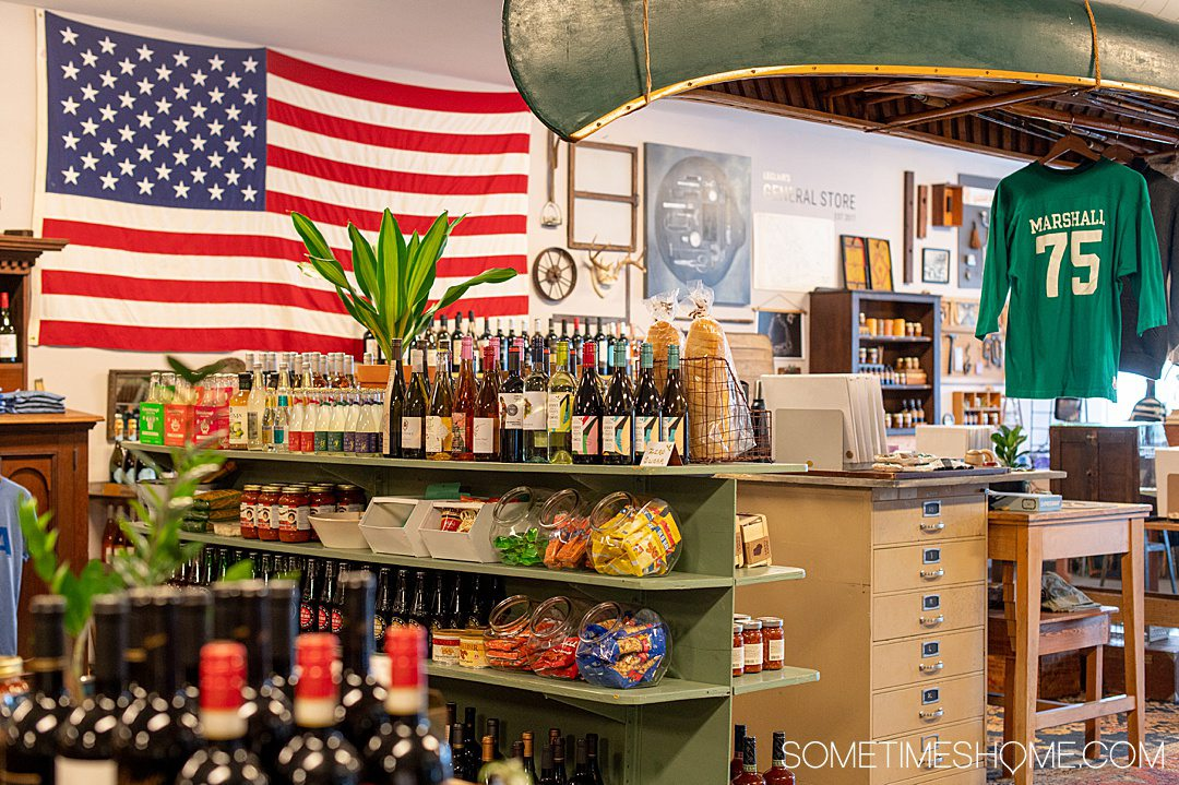 Image of an American flag, an upside down canoe hanging from the ceiling and products at LeClair's general store.