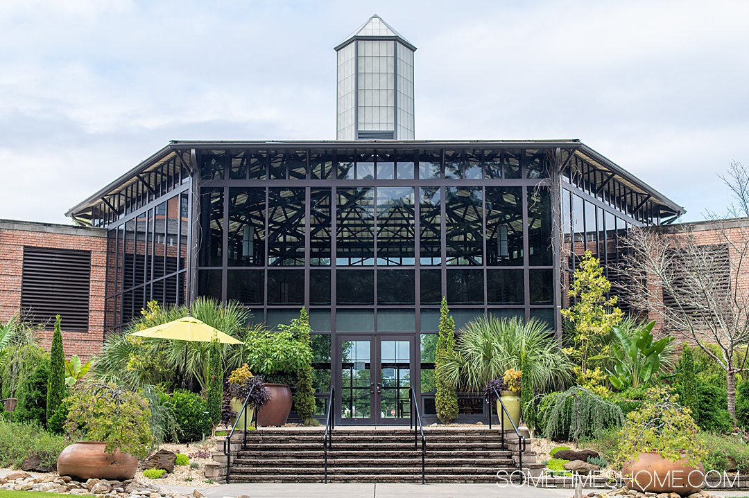 Glass facade of the main building at Cape Fear Botanical Gardens in Fayetteville, NC, surrounded by plants.