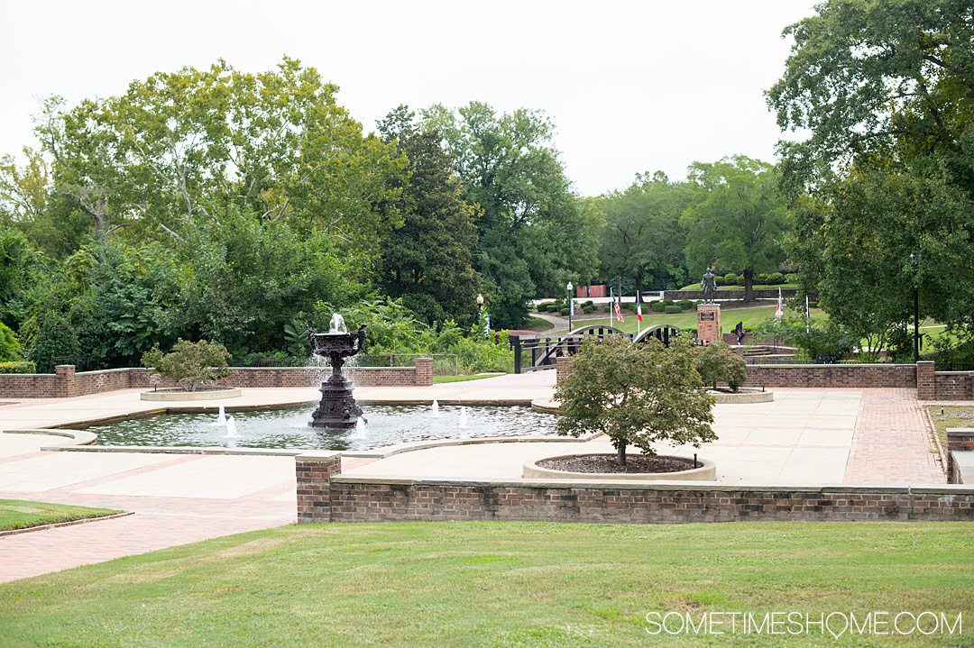 View of a park fountain and green grass and trees in Fayetteville, NC.