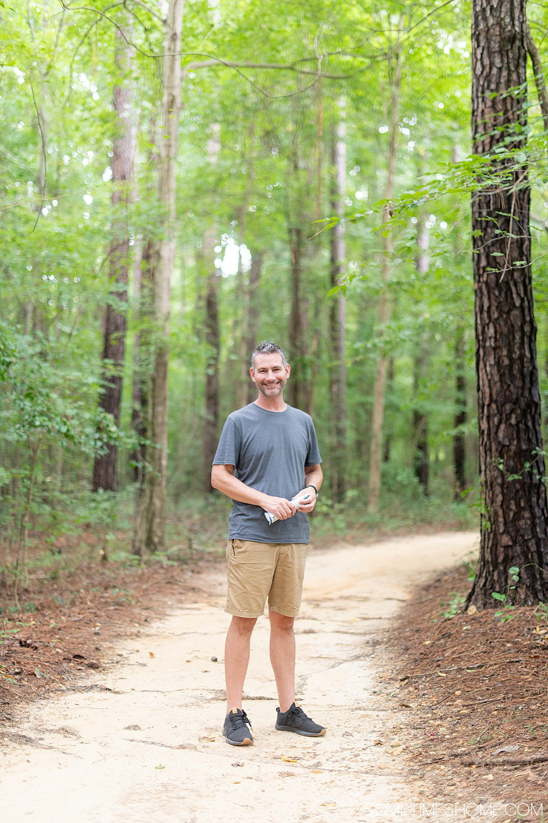 A man on a dirt walkway surrounded by tall trees at Cape Fear Botanical Gardens in Fayetteville, NC.