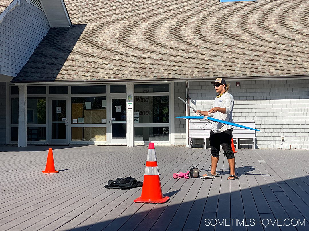 Image of a man with a small hang glider model and two orange traffic cones on a grey balcony for a Hang Gliding in the Outer Banks post.