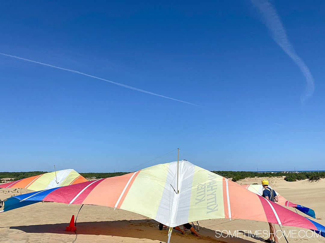 Hang gliding in the Outer Banks of NC with colorful red, yellow and blue hang gliders and tan colored sand dunes and blue sky at Jockey's Ridge State Park in Nags Head.