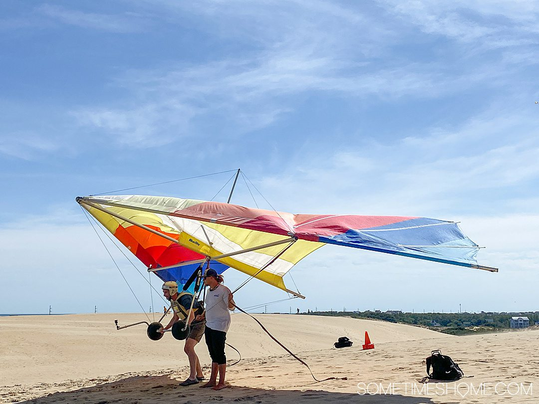 Colorful hang gliders and people with tan colored sand dunes and blue sky at Jockey's Ridge State Park in Nags Head, of the Outer Banks in NC.