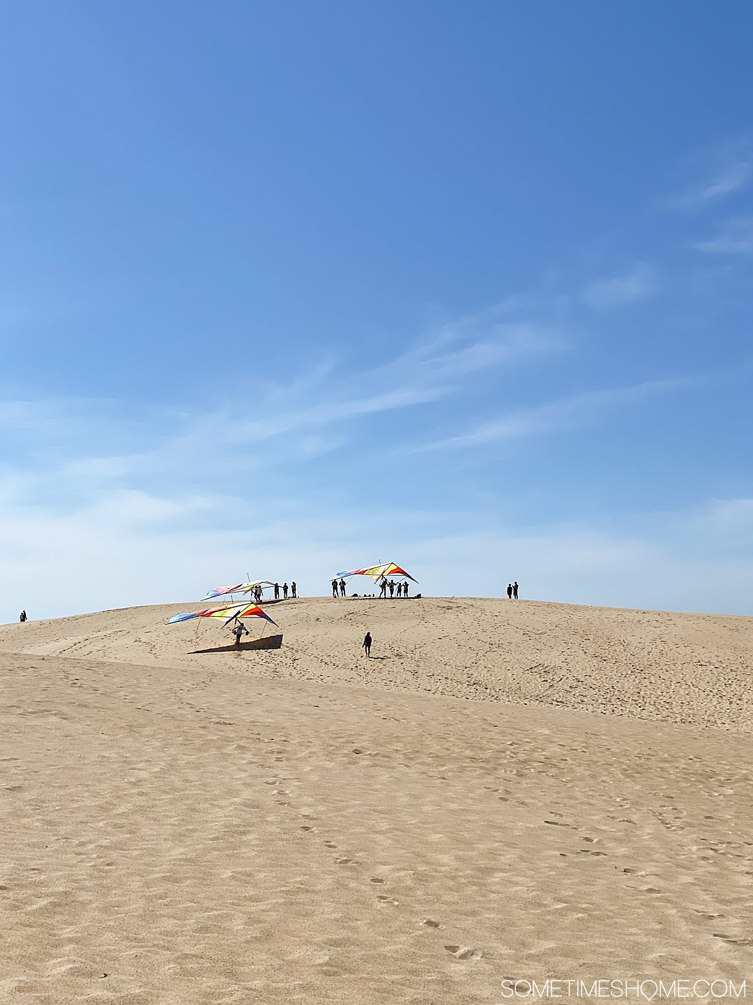 Hang gliders and people in the distance with tan colored sand dunes and blue sky at Jockey's Ridge State Park in Nags Head, of the Outer Banks in NC.