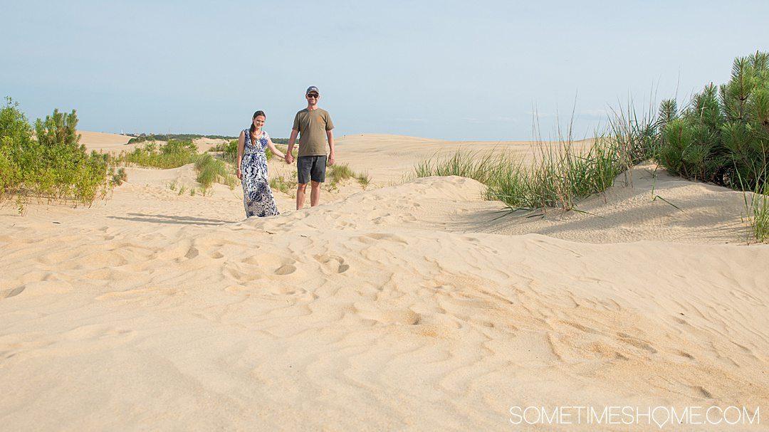 A couple in the sand dunes of Jockey's Ridge State Park in Nags Head, North Carolina in the Outer Banks.