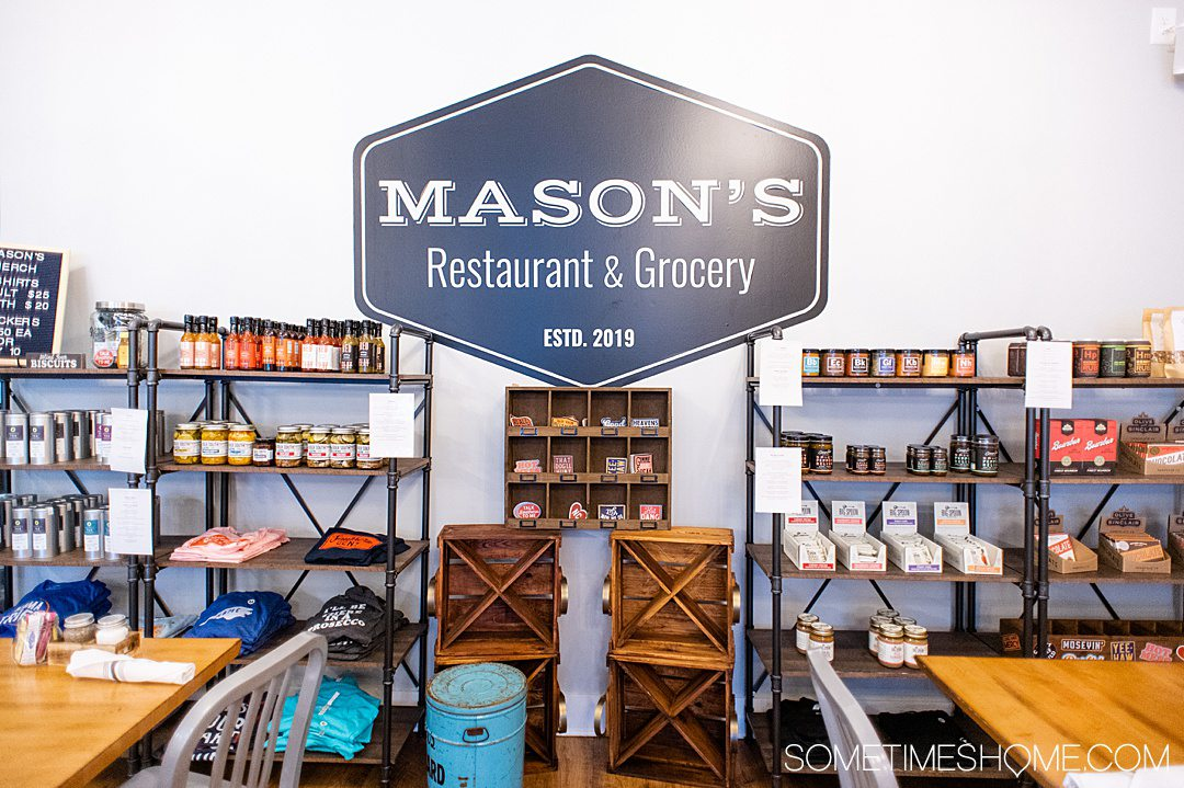 "A sign that reads ""Mason's Restaurant and Grocery"" with shelves of products."