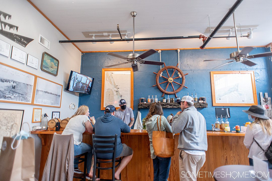 People inside at a wooden beach bar with a captain's wheel on a blue painted wall an television on the left side, at Outer Banks Distilling .