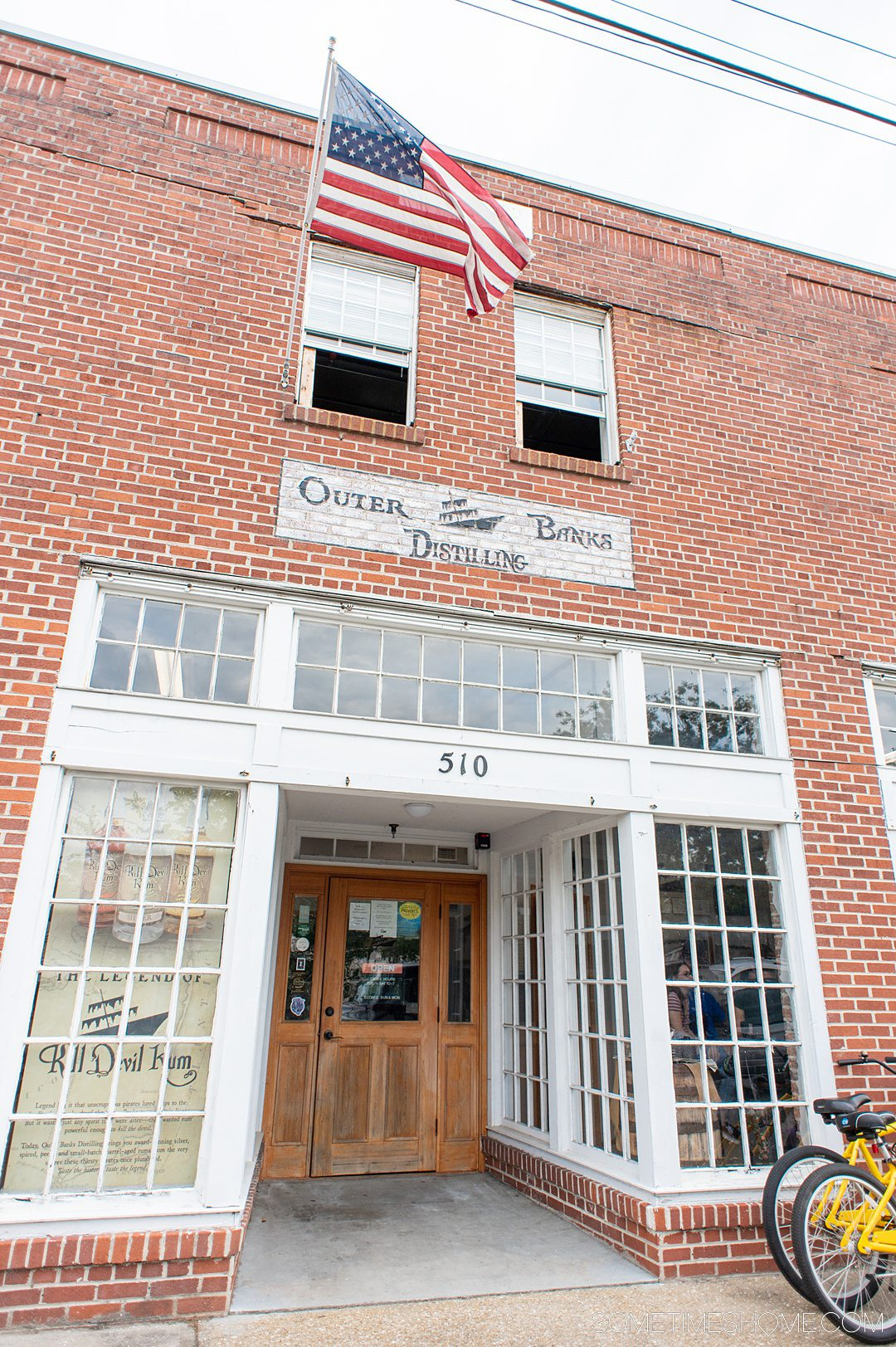 """The facade of a brick and white-painted-wood building that says """"Outer Banks Distilling"""" on the outside sign."""