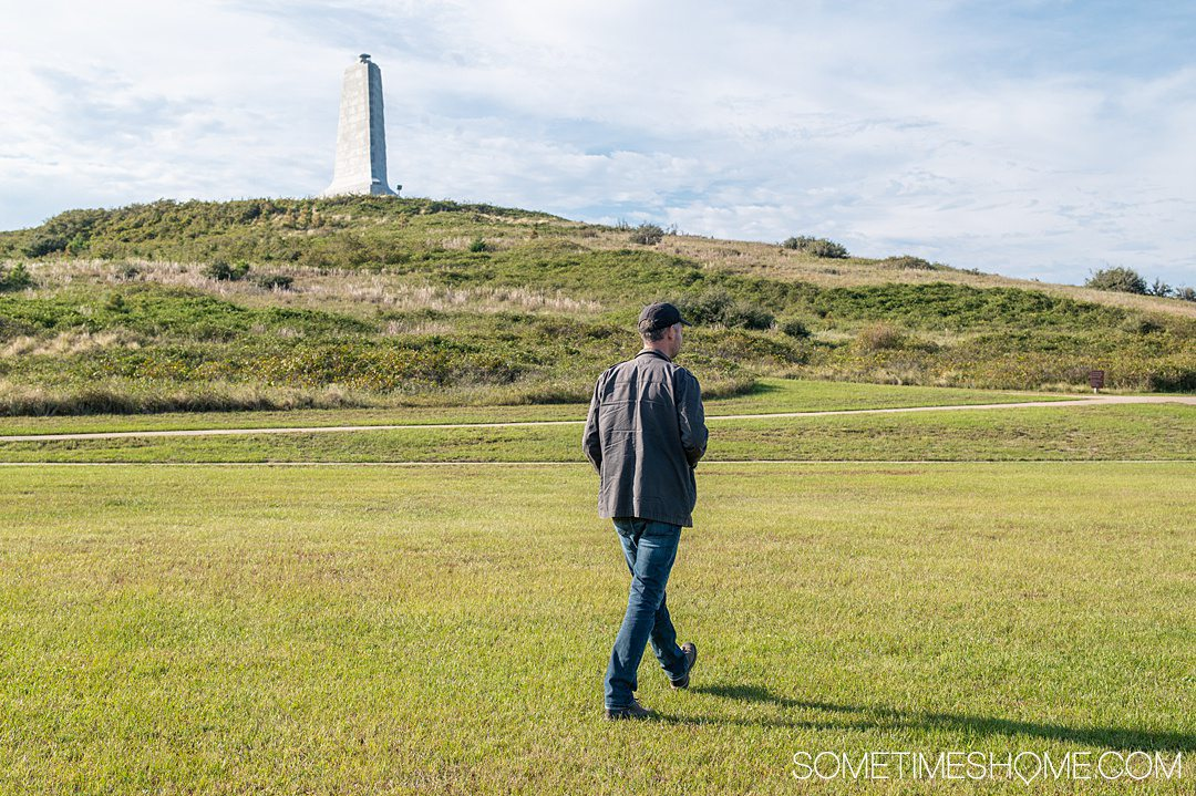 A man walking on a green lawn with a white monument on a hill in the background in the Outer Banks in October.
