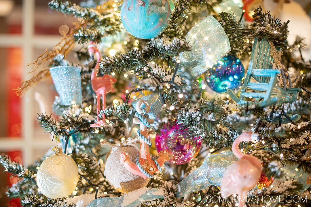 Close up photo of holiday ornaments, including blue, peach and pink pieces, on a colorful holiday tree.