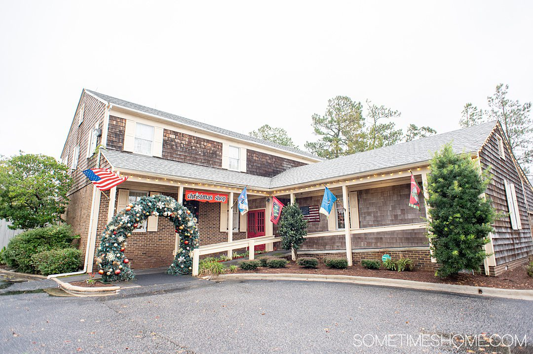 Building with an overside Christmas wreath as an entry way and porch, with wood shingles and light yellow shutters, called The Christmas Shop in the Outer Banks in NC.