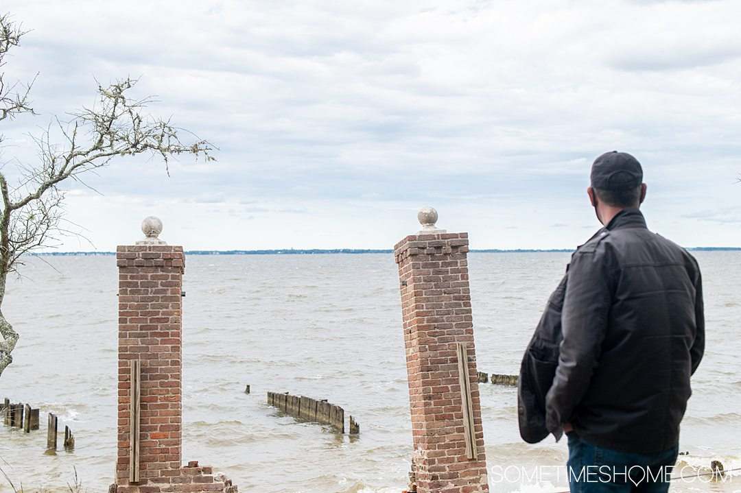 A man looking out to the water and two square brick pillars on Roanoke Island at the Elizabethan Gardens in the Outer Banks.