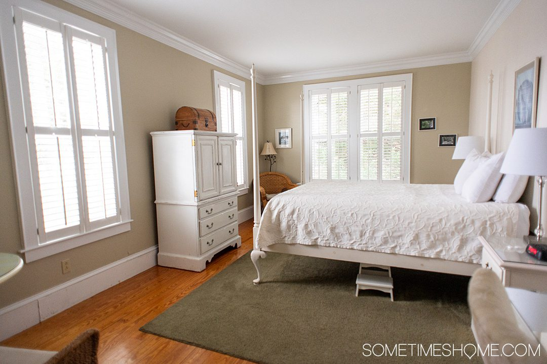 Hotel room with a white armoire on the left and white four-poster bed on the right on top of a sage green area rug at the Tranquil House Inn in the Outer Banks.
