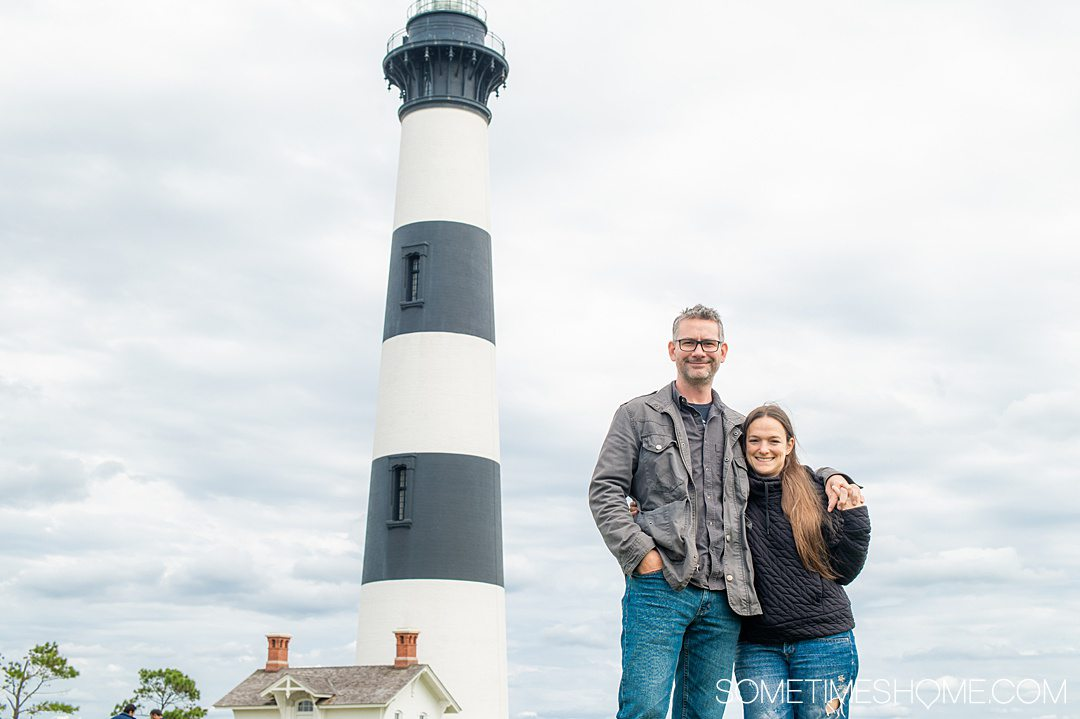 A man and a woman on the right of the photo with a black and white horizontally striped lighthouse on the left in the Outer Banks, at Cape Hatteras North Carolina.