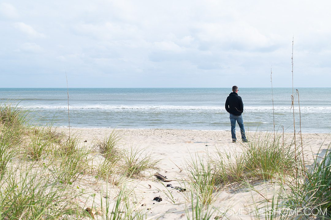 A man on the seashore at Hatteras Beach in the Outer Banks with greenery in the foreground and beach and blue sky in the background.