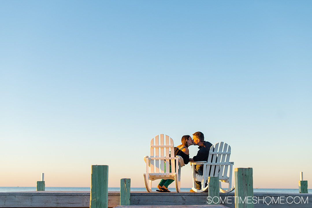 A couple kissing in white Adirondack chairs on a dock, with a blue sky fading into pink and orange during sunset at The Inn on Pamlico Sound.