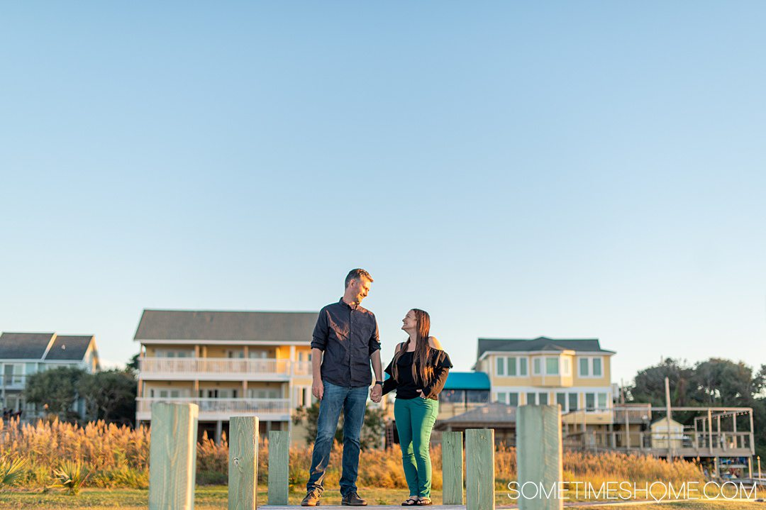 A couple on a dock with a yellow painted hotel in the distance, and golden hour during sunset at the Inn on Pamlico Sound in the Outer Banks in October in Buxton, NC.
