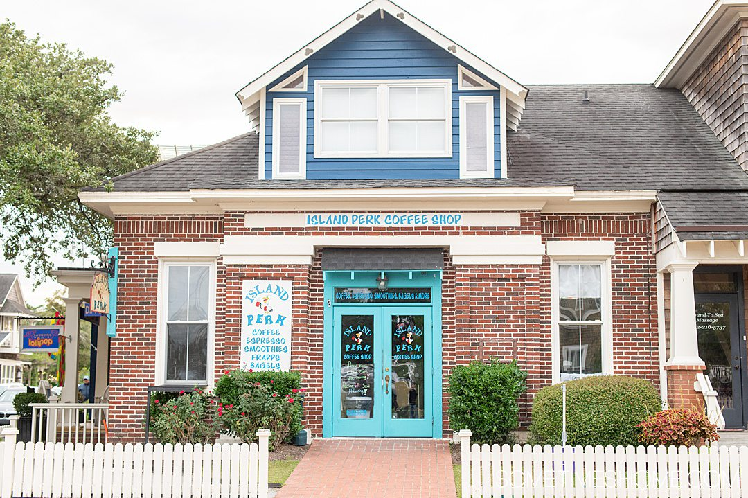 Island Perk Coffee Shop with a brick building and turquoise doors and a white picket fence in downtown Manteo in the Outer Banks.