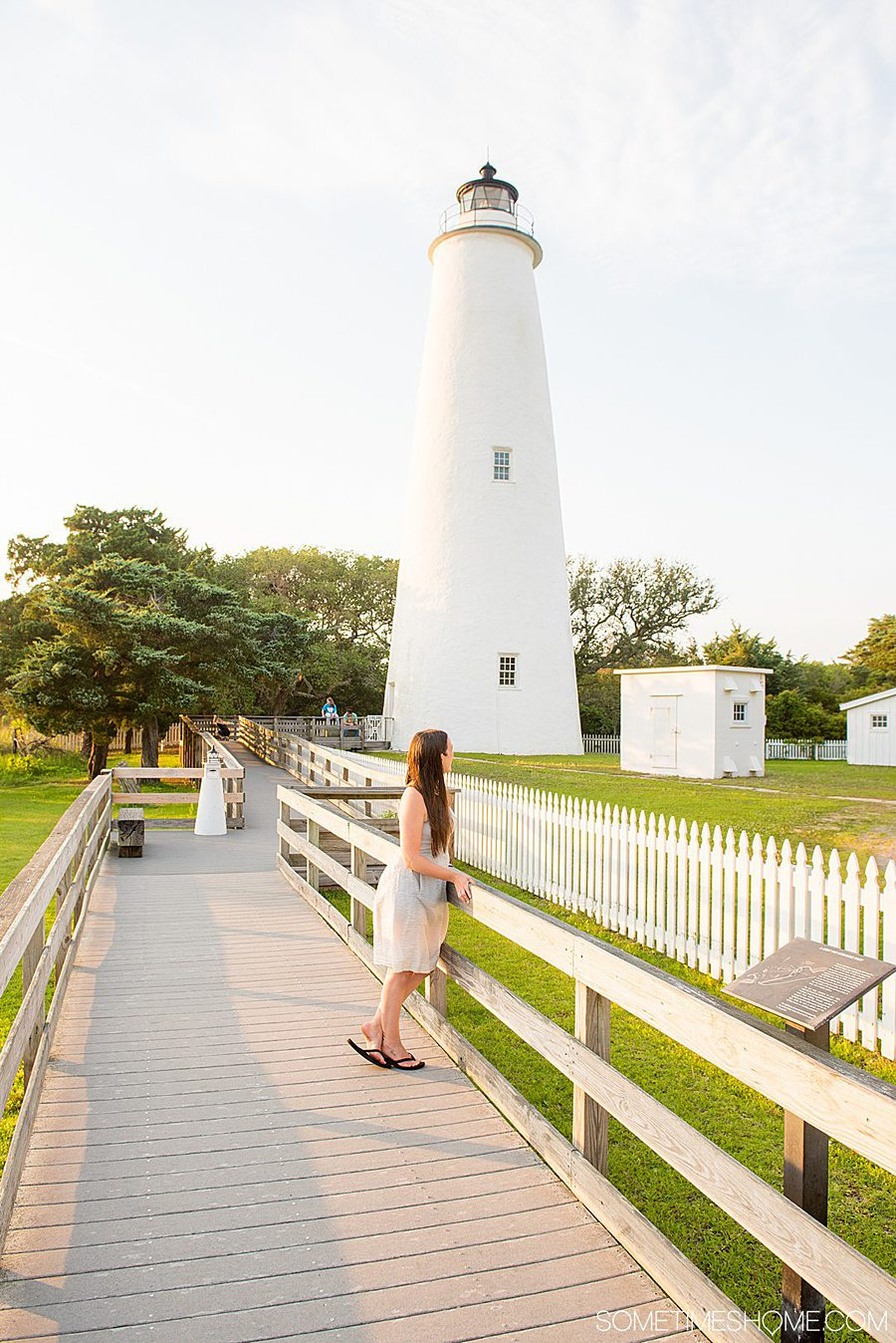 A woman in a dress in the distance looking at a small white lighthouse behind her with green grass and green trees around it, and fences.