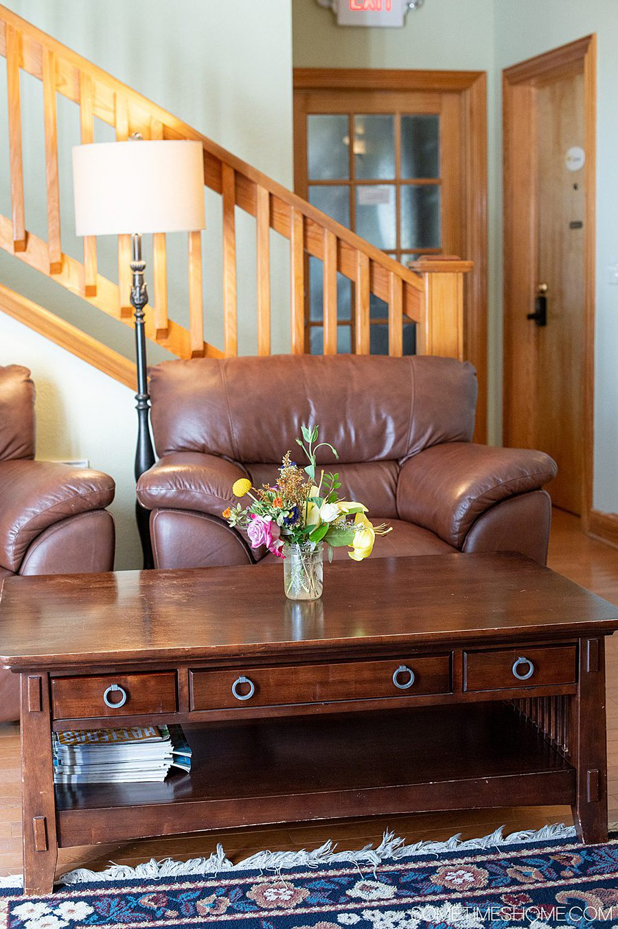Two brown leather chairs and a brown coffee table in front of a staircase in a room. The table has a vase with colorful flowers in a room. There is a floor lamp to the left of the right chair.