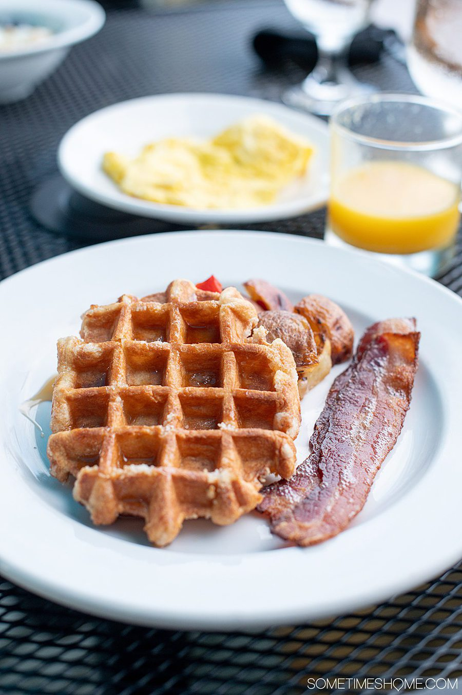 A plate of waffles and bacon, with potatoes, eggs and orange juice, in the background in the Outer Banks at Cafe Pamlico restaurant.