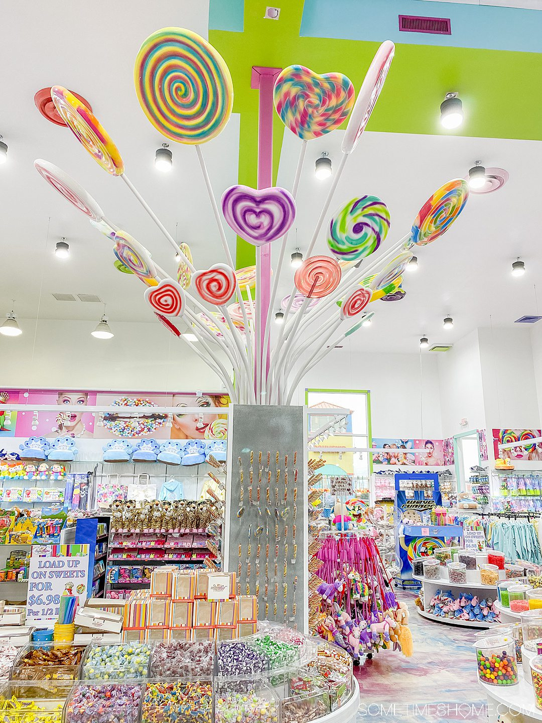 Display inside a candy store with colorful lollipops coming out of the top of a column.