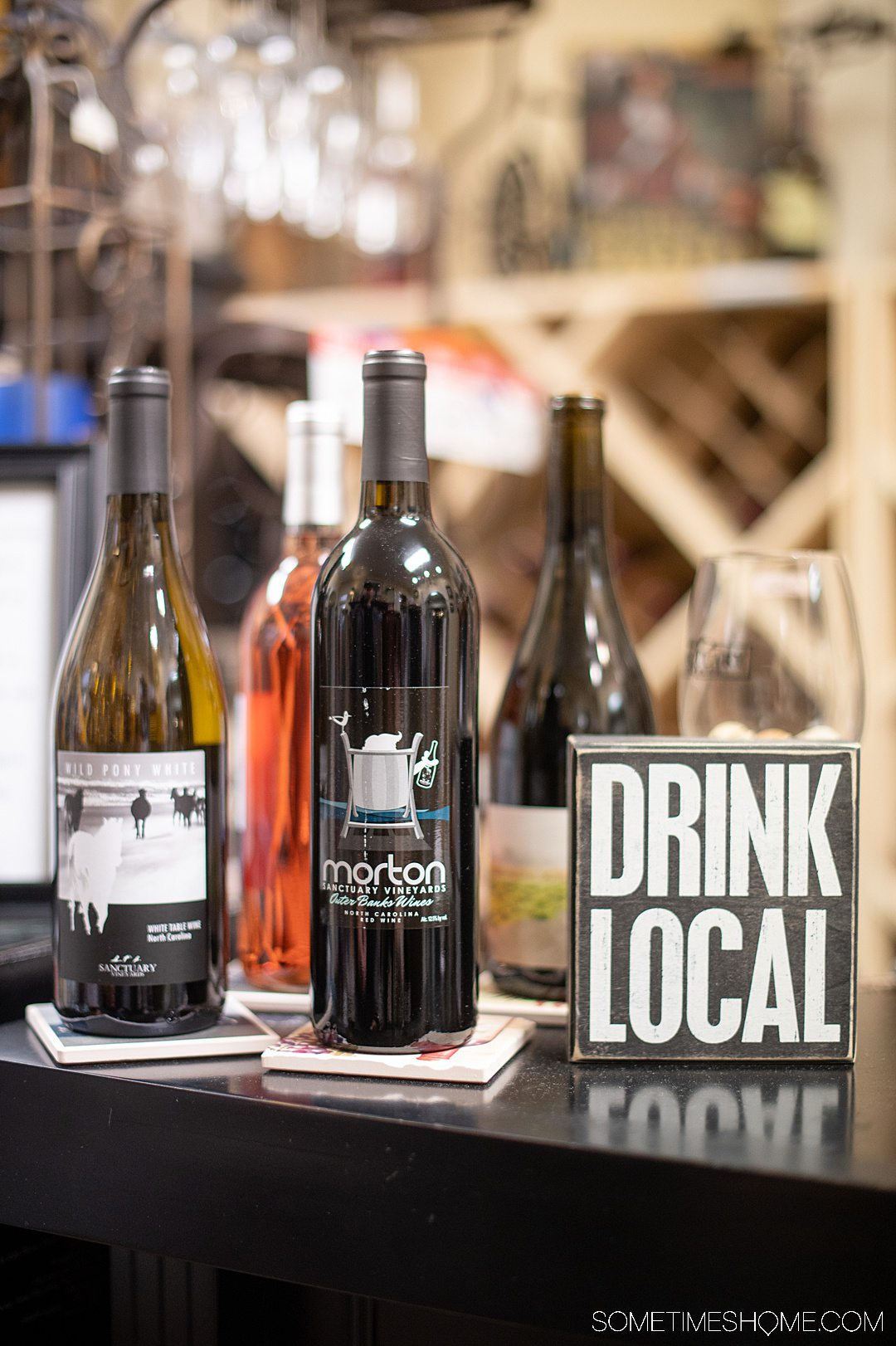 """A """"Drink local"""" sign and several wine bottles set up for a wine tasting inside a shop in the Outer Banks for indoor activities."""